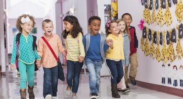 A multi-ethnic group of seven children holding hands, walking through their school hallway, laughing and smiling.  They are in kindergarten or preschool.  The little African American boy in the middle is shouting, leading the way.